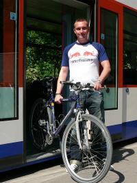 Mann mit Fahrrad steigt aus Straßenbahn